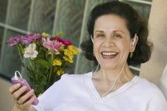 Ältere Frau, die Musik auf MP3-Player hört Stockfotos
