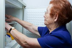 Ältere Frau, die nach Nahrung im Kühlraum sucht stockbild