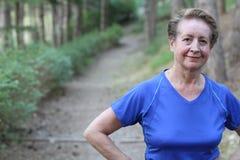 Ältere Frau, die nachdem dem Trainieren im Park stillsteht Lizenzfreie Stockbilder