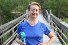 Ältere Frau, die nachdem dem Trainieren im Park stillsteht Lizenzfreies Stockbild