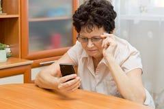 Ältere Frau, die nah dem Schirm des Telefons, versuchend, zu sehen betrachtet, was dort geschrieben wird Stockfotografie