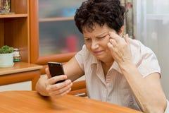 Ältere Frau, die nah dem Schirm des Telefons, versuchend, zu sehen betrachtet, was dort geschrieben wird Lizenzfreie Stockfotografie