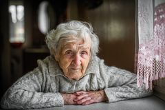 Ältere Frau, die nahe dem Fenster sitzt lizenzfreie stockfotos