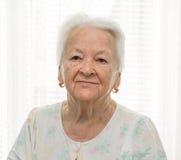 Ältere Frau, die nahe dem Fenster sitzt Lizenzfreie Stockfotografie