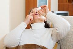 Ältere Frau, die nasale Tropfen tropft Stockfoto