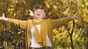 Ältere Frau, die oben den Herbstlaub, sorgloses Leben genießend, sicheres hohes Alter wirft stock video