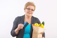 Ältere Frau, die Obst und Gemüse in der Einkaufstasche und in Kreditkarte, zahlend für den Einkauf hält lizenzfreie stockfotos