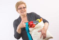 Ältere Frau, die Obst und Gemüse in der Einkaufstasche und in Kreditkarte, zahlend für den Einkauf hält lizenzfreie stockbilder