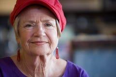 Ältere Frau, die Red Hat trägt stockbilder