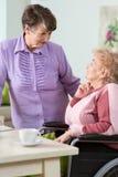 Ältere Frau, die Rollstuhl verwendet Stockbild