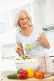 Ältere Frau, die Salat in der modernen Küche zubereitet Lizenzfreies Stockfoto