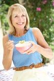 Ältere Frau, die Schüssel Frühstückskost aus Getreide genießt Stockbilder