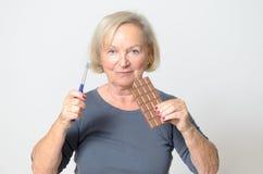 Ältere Frau, die Schokoriegel und Zahnbürste hält Stockfotografie