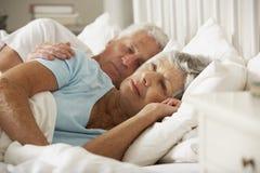 Ältere Frau, die Schwierigkeit beim Schlafen im Bett mit Ehemann hat stockbild