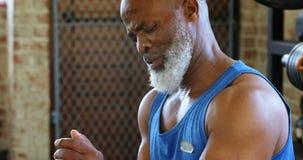 Ältere Frau, die sein smartwatch im Eignungsstudio 4k trägt stock video