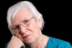 Ältere Frau, die sich an Hand mit schwarzem Hintergrund lehnt Lizenzfreies Stockfoto