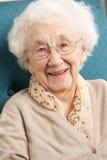 Ältere Frau, die sich zu Hause im Stuhl entspannt Stockfotos