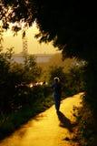 Ältere Frau, die in Sonnenuntergang geht Stockfotos
