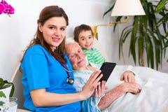 Ältere Frau, die Spaß mit Familie und Doktor hat Lizenzfreie Stockbilder