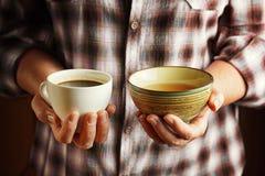 Ältere Frau, die Tasse Kaffee und Tasse Tee hält Stockfotografie