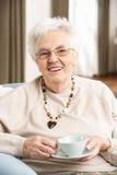 Ältere Frau, die Tasse Tee genießt Lizenzfreie Stockfotos