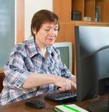 Ältere Frau, die Tastatur verwendet Stockbild