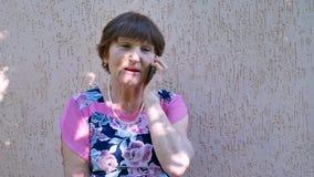 Ältere Frau, die am Telefon außerhalb des nahen Hauses spricht stock footage