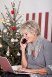 Ältere Frau, die Telefon auf Weihnachtsabend verwendet Stockfotografie