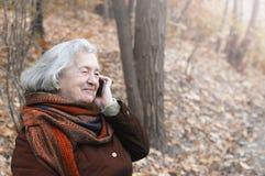 Ältere Frau, die am Telefon in einem Herbstpark spricht lizenzfreie stockfotos