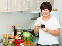 Ältere Frau, die Telefon schaut lizenzfreies stockbild