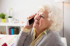 Ältere Frau, die am Telefon spricht stockfotos