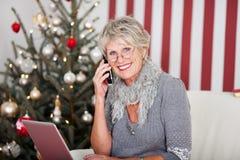 Ältere Frau, die am Telefon am Weihnachten plaudert Lizenzfreie Stockfotos