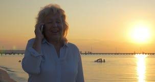 Ältere Frau, die Telefongespräch auf Strand bei Sonnenuntergang hat stock video footage