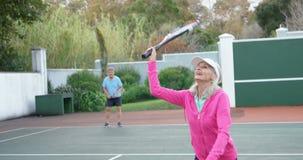 Ältere Frau, die Tennis im Tennisplatz 4k spielt stock footage