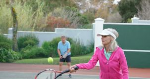 Ältere Frau, die Tennis im Tennisplatz 4k spielt stock video