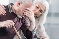 Ältere Frau, die um Ehemann mit starken Kopfschmerzen sich kümmert lizenzfreie stockbilder