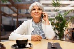 Ältere Frau, die um Smartphone am Straßencafé ersucht lizenzfreie stockfotografie