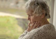 Ältere Frau, die Umkippen durch ein Fenster schaut stockbild