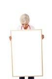 Ältere Frau, die unbelegtes Plakat anhält Stockfotografie