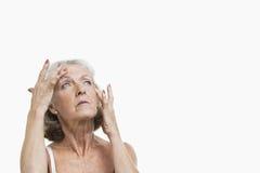 Ältere Frau, die unter Kopfschmerzen gegen weißen Hintergrund leidet Stockbilder