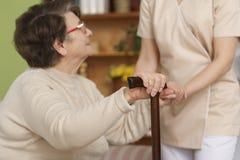 Ältere Frau, die versucht, oben zu stehen lizenzfreies stockfoto