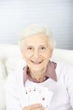Ältere Frau, die vier Asse hält Stockbilder