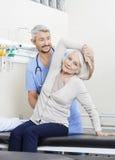 Ältere Frau, die vom Physiotherapeuten With Arm Exercise unterstützt wird stockfotos