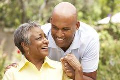 Ältere Frau, die von Adult Son umarmt wird Stockfoto