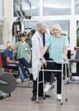 Ältere Frau, die von Doktor At Rehab Center unterstützt wird stockfotos