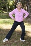 Ältere Frau, die vor Übung im Park aufwärmt stockfotos