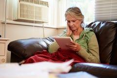 Ältere Frau, die warme Unterdecke mit Fotografie hält Stockbilder
