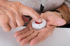 Ältere Frau, die Warnungs-Knopf bedrängt Stockbild
