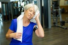Ältere Frau, die weg vom Schweiß weg von der Stirn abwischt Stockfotos