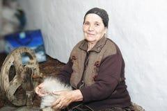 Ältere Frau, die woollen Garn kardiert stockfotografie